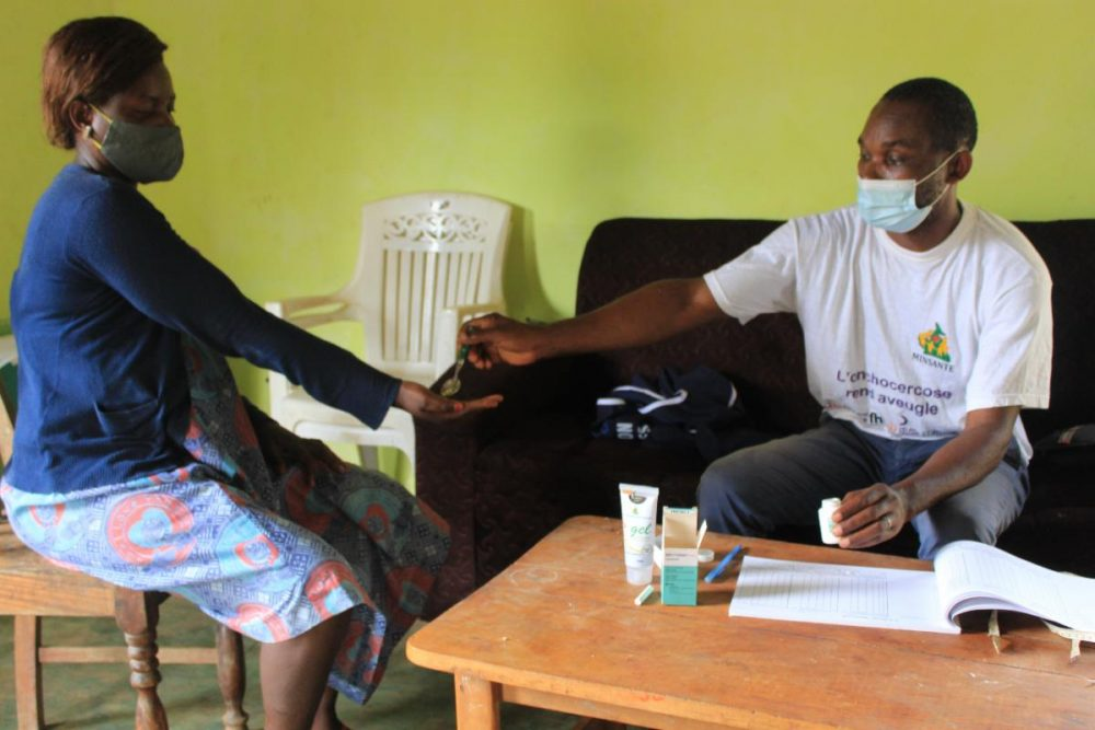 A man gives Mectizan pills to a woman in Cameroon. Both are wearing masks.