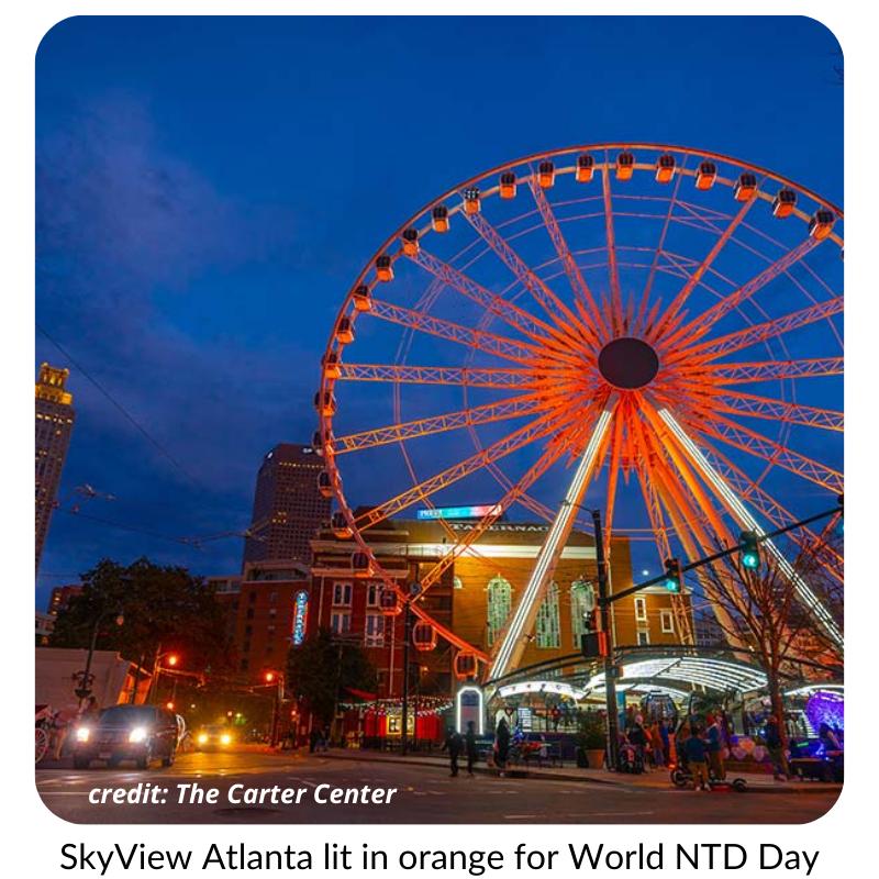 Photo of a Ferris wheel in Atlanta. It is illuminated in orange light.